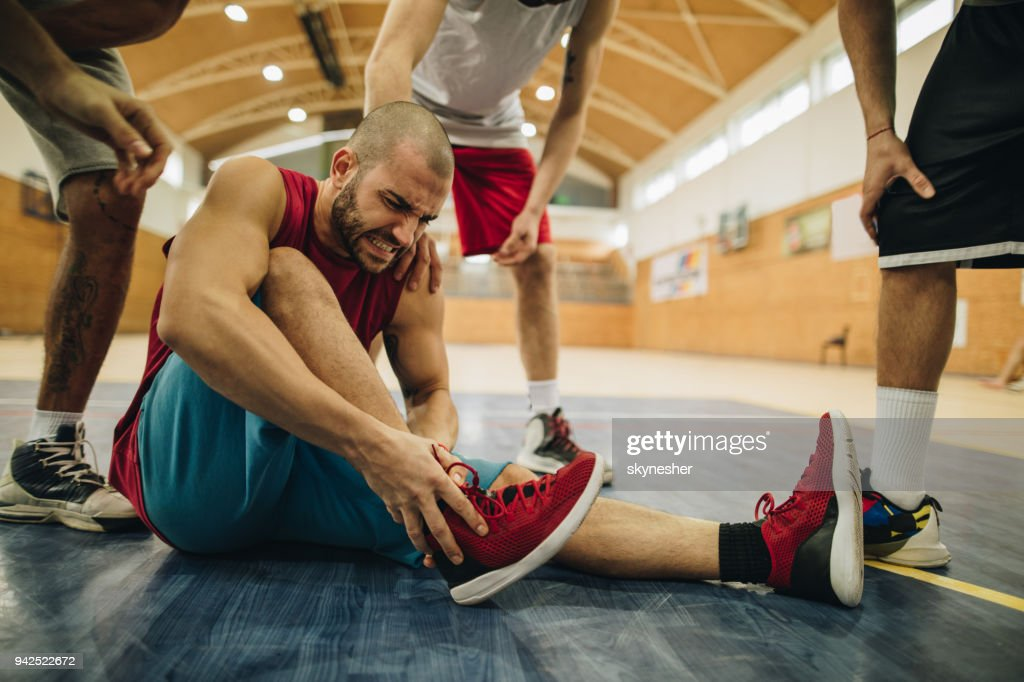 Injured basketball player holding his ankle in pain on the court. : Stock Photo