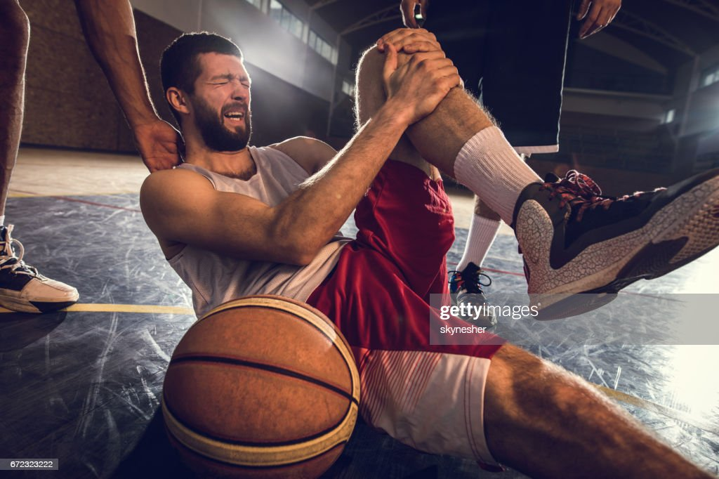 Injured basketball player holding his leg in pain on the court. : Stock Photo