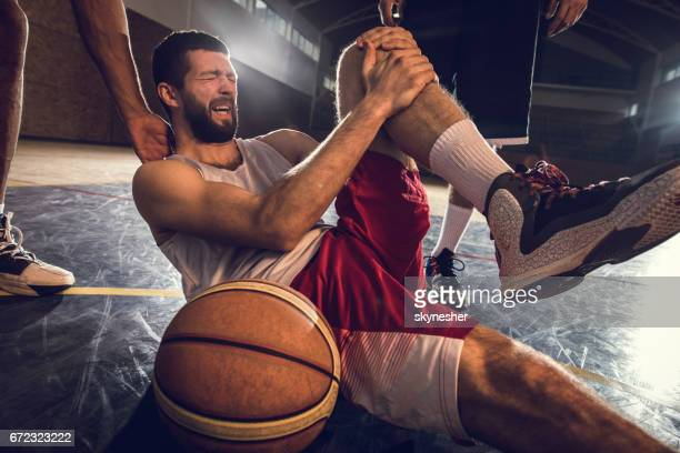injured basketball player holding his leg in pain on the court. - personal injury stock photos and pictures