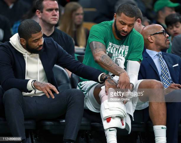 Injured Boston Celtics guard Kyrie Irving left aids teammate Marcus Morris as he wraps his right knee on the bench in the first half The Boston...