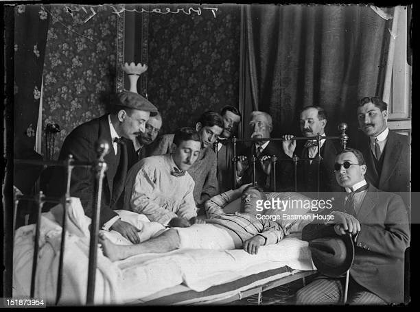 Injured bullfighter in bed being attended by doctor, ca. 1908.