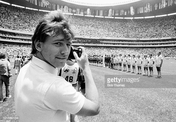 Injured captain Bryan Robson of England is pictured behind the camera as England and Argentina line up prior to their World Cup QuarterFinal match...