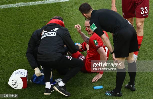 Injured Cologne's German midfielder Marius Wolf is treated by medical personnel during the German relegation Bundesliga football match between first...