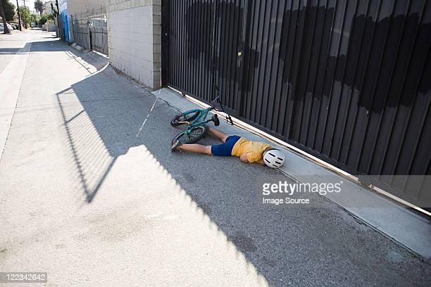 Injured cyclist lying on sidewalk