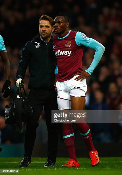 A injured Diafra Sakho of West Ham United is assisted by physio Dominic Rogan during the Barclays Premier League match between West Ham United and...