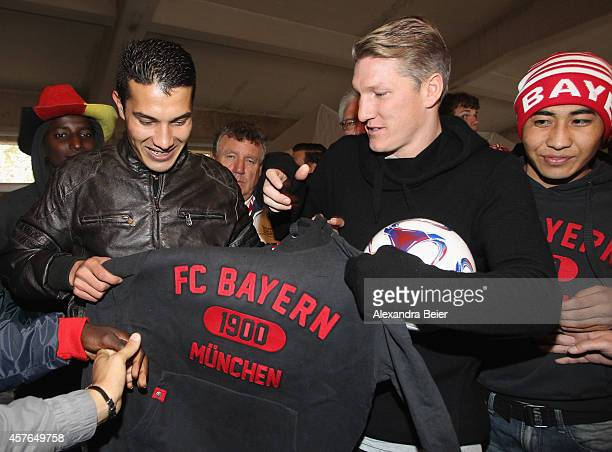 Injured FC Bayern Muenchen midfielder Bastian Schweinsteiger hands over Adidas gear to a refugee in the refugee camp and the former German barracks...