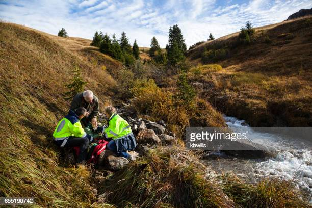injured girl tended by swiss mountain rescue while concerned grandfather watches on - rescue stock pictures, royalty-free photos & images