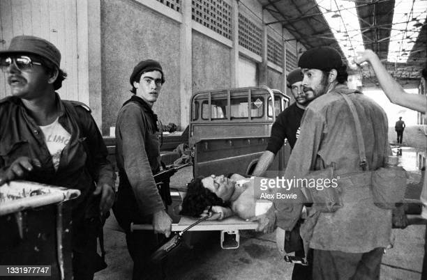 Injured guerrilla fighter from the Sandinista National Liberation Front is carried by comrades to a Red Cross aid station near the border between...
