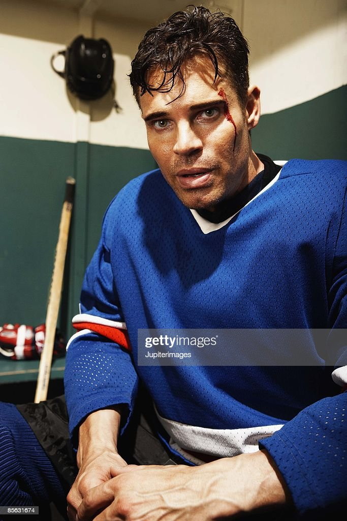 Injured hockey player in locker room : Stock Photo