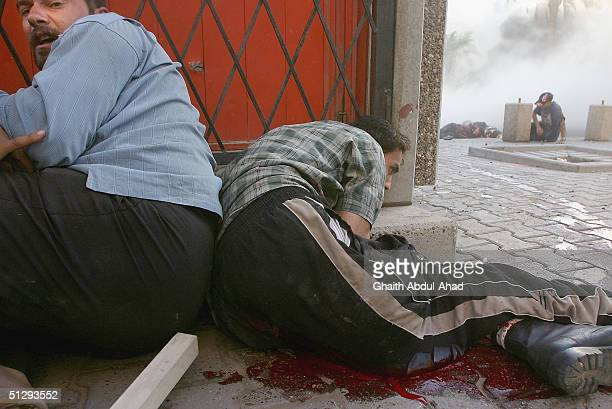Injured Iraqi civilian take cover on September 12 2004 in Haifa Street Baghdad Iraq Fighting broke out in the early hours of September 12 2004 as...