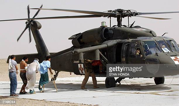 Injured Iraqis classified as enemy prisoners of war walk into a medevac helicopter as they are transferred from the 28th Combat Support Hospital,...