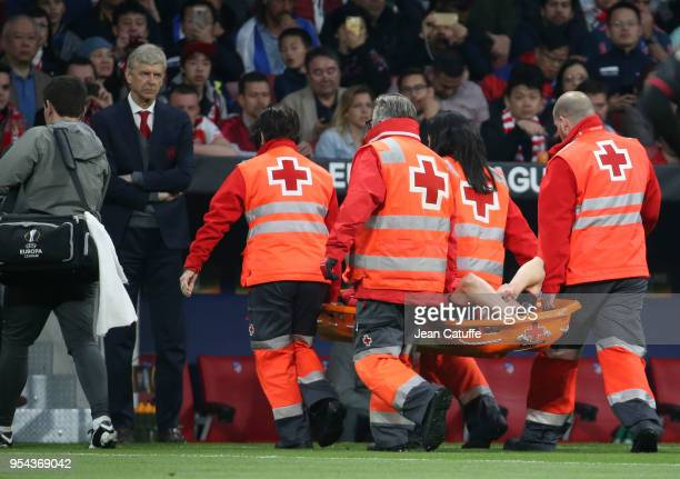 Injured Laurent Koscielny of Arsenal leaves the pitch on a stretcher in front of coach of Arsenal Arsene Wenger during the UEFA Europa League Semi...