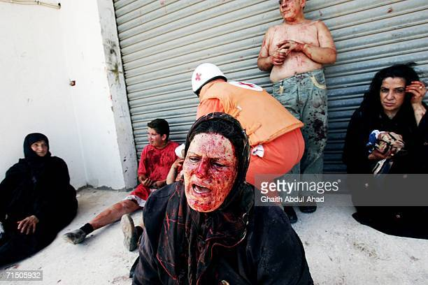 Injured Lebanese people are seen on the ground after a rocket from an Israeli aircraft hit their van as they fled their village July 23, 2006 in...