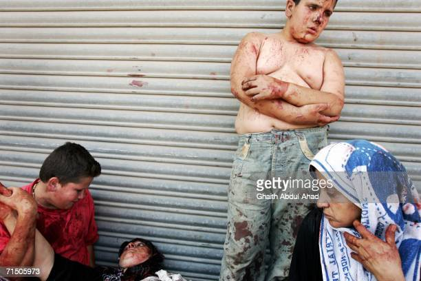 Injured Lebanese people are seen on the side of the street after a rocket from an Israeli aircraft hit their van as they fled their village July 23,...