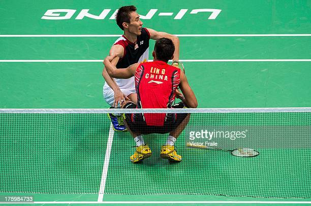 Injured Lee Chong Wei of Malaysia is attended to by Lin Dan of China during the men's singles final match during the Badminton World Championships at...