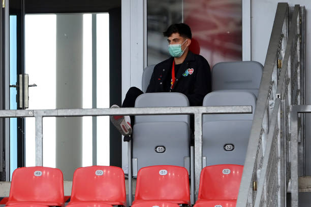 Injured Leverkusen's German midfielder Kai Havertz wearing a face mask sits in grandstand as he attends the German first division Bundesliga football...