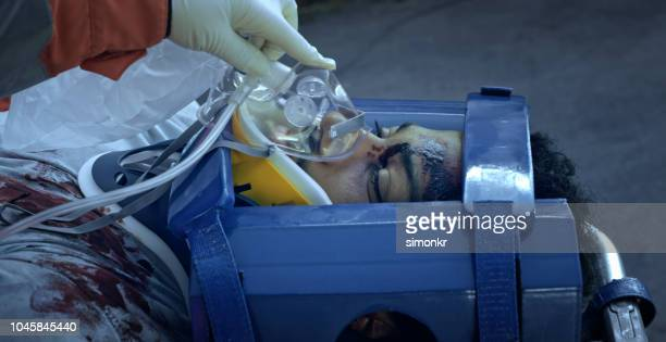 injured male being given an oxygen mask while lying with immobilized head and neck - breathing device stock pictures, royalty-free photos & images