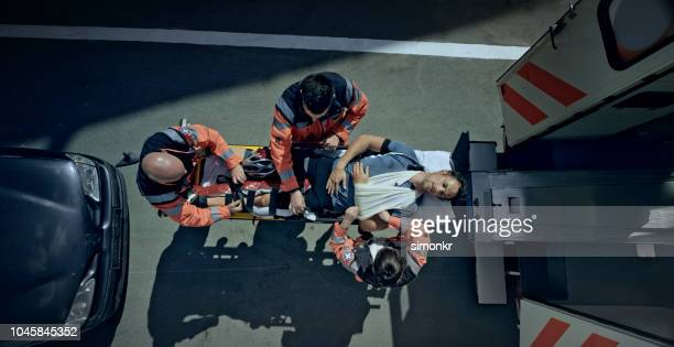 injured male cyclist being loaded into ambulance on stretcher - barella foto e immagini stock