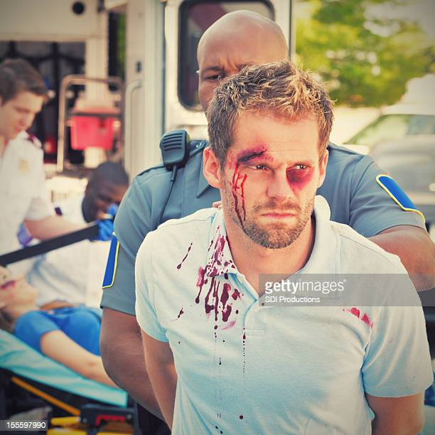 injured man being arrested by police officer - beaten up stock pictures, royalty-free photos & images