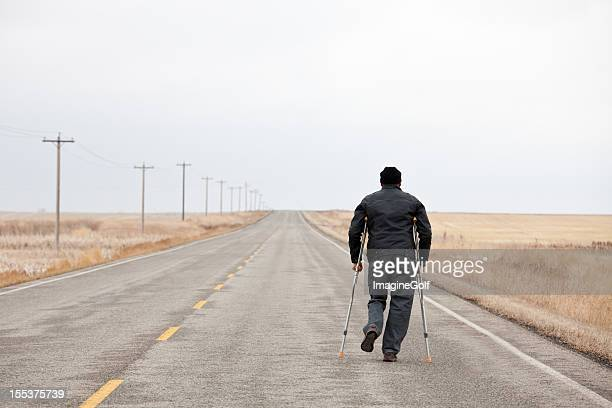 injured man walking down a desolate highway with crutches - man crutches stock photos and pictures