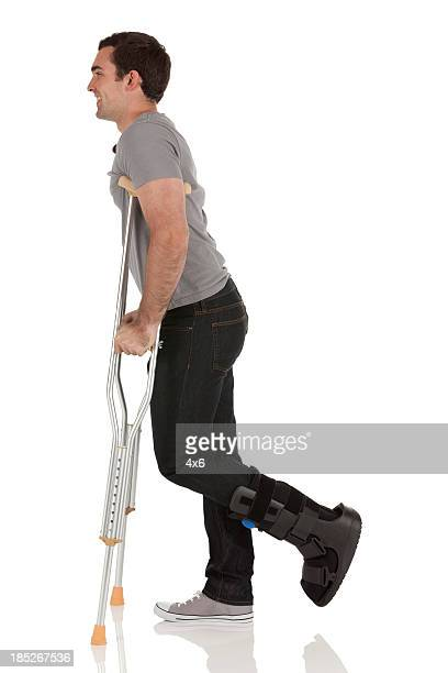 injured man walking with the help of crutches - man crutches stock photos and pictures