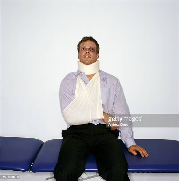Injured Man with a Shocked Expression Wearing a Neck Brace and Arm Sling