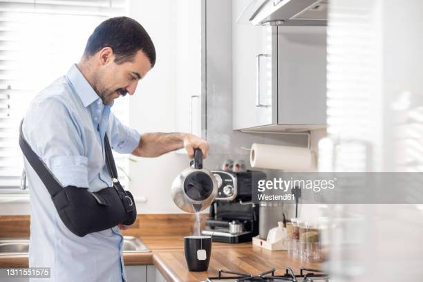 injured man with arm sling pouring tea in cup through kettle in kitchen at home - side view stock pictures, royalty-free photos & images