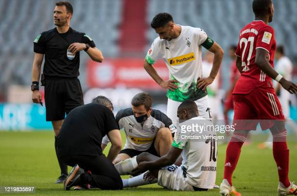 Injured Marcus Thuram of Borussia Moenchengladbach is checked by medical staff during the Bundesliga match between FC Bayern Muenchen and Borussia...