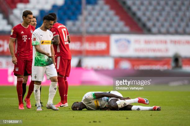 Injured Marcus Thuram of Borussia Moenchengladbach lies on the pitch during the Bundesliga match between FC Bayern Muenchen and Borussia...