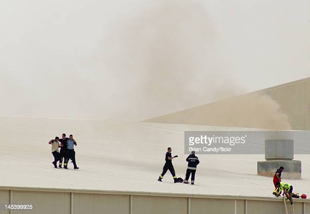 Injured member of the emergency services is helped across a roof as smoke from a fire rises above them at the Villaggio mall on May 28, 2012 in Doha,...