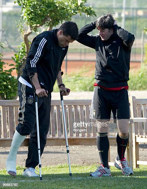 Injured Michael Ballack speaks with head coach Joachim Loew during the German National Team training session at Verdura Golf Spa Resort on May 18...