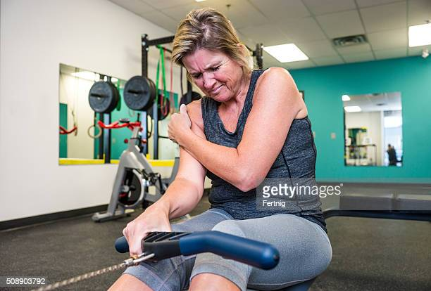 Injured middle-aged woman working out on a rowing machine