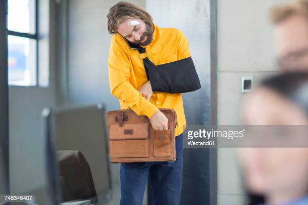 injured office employee adjusting his bag - arm sling stock pictures, royalty-free photos & images