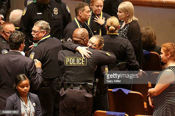Injured officer Misty McBride hugs a fellow officer during the Interfaith Memorial honoring the Dallas shooting victims at The Morton H Meyerson...
