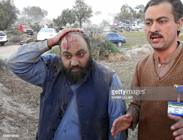 Injured Pakistani political party workers leave the site after a bomb blast in Bannu on November 26 2015 At least two people were killed when a...