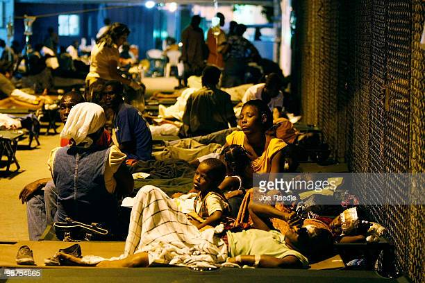 Injured people are seen at a makeshift field hospital on January 13 2010 in PortauPrince Haiti Planeloads of rescuers and relief supplies headed to...