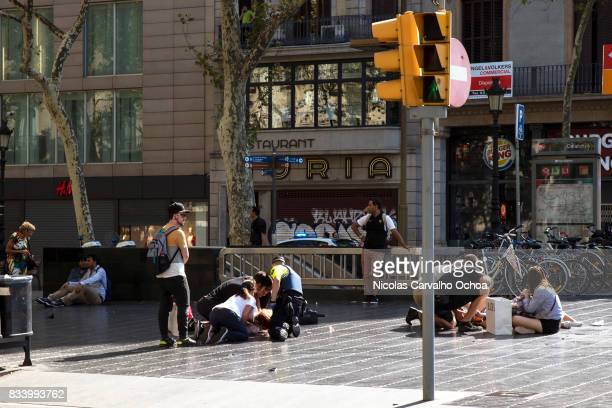 Injured people are tended to near the scene of a terrorist attack in the Las Ramblas area on August 17 2017 in Barcelona Spain Officials say 13...