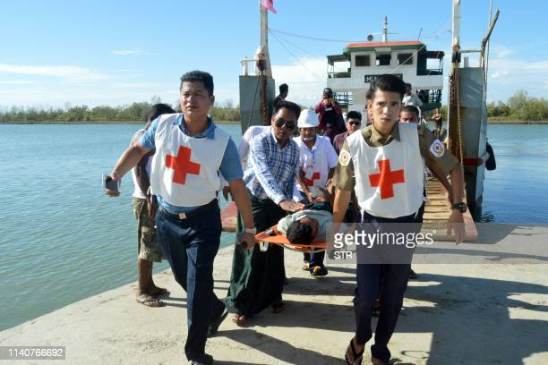 Injured people from Kyauk Tan village in Rathedaung township are carried on stretchers as they arrive in Rakhine state's capital Sittwe in western...