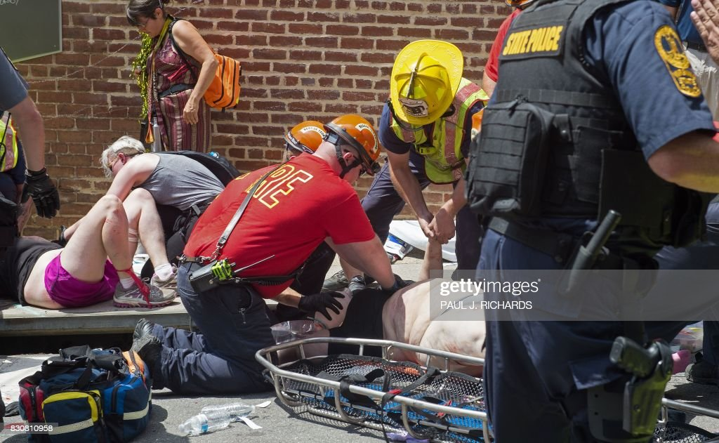 TOPSHOT - Injured people receive first-aid after a car accident ran into a crowd of protesters in Charlottesville, VA on August 12, 2017. A vehicle plowed into a crowd of people Saturday at a Virginia rally where violence erupted between white nationalist demonstrators and counter-protesters, witnesses said, causing an unclear number of injuries. /