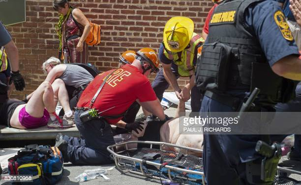TOPSHOT Injured people receive firstaid after a car accident ran into a crowd of protesters in Charlottesville VA on August 12 2017 A vehicle plowed...
