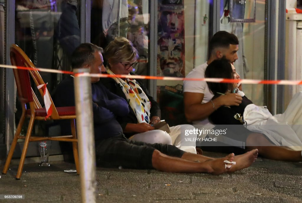 injured people sit on the pavement inside a cordoned off area at the