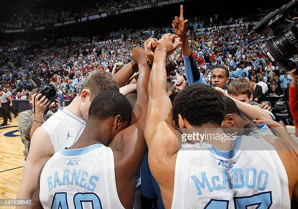 Injured player John Henson of the North Carolina Tar Heels holds up the sign as he huddels up with teammates including Harrison Barnes and James...