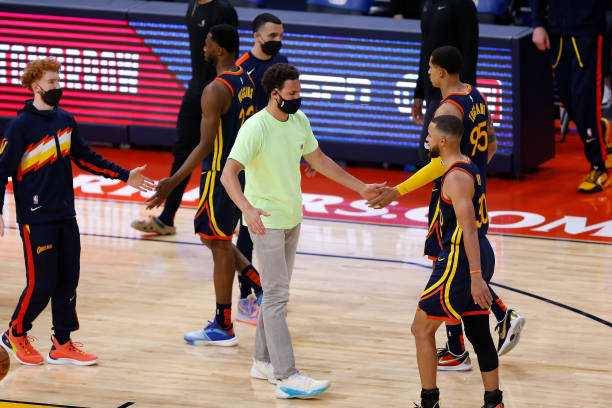 Injured player Klay Thompson of the Golden State Warriors greets teammates during a timeout in the fourth quarter of the NBA Play-In Tournament game...
