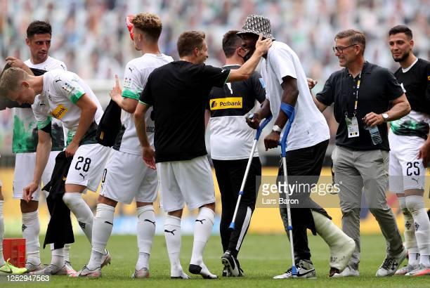 Injured player Marcus Thuram of Moenchengladbach celebrates with his team mates after winning the Bundesliga match between Borussia Moenchengladbach...
