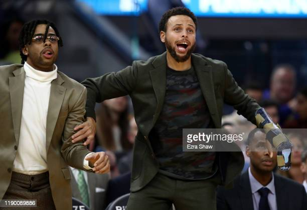 Injured players D'Angelo Russell and Stephen Curry of the Golden State Warriors react on the bench during their game against the Oklahoma City...