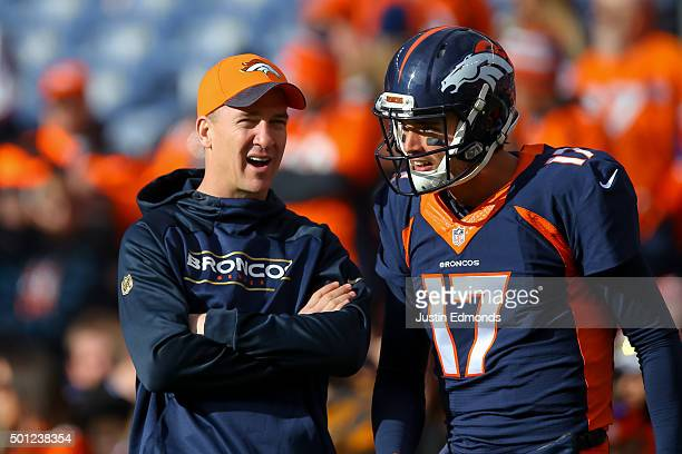 Injured quarterback Peyton Manning of the Denver Broncos left has a word with quarterback Brock Osweiler as players warm up before a game against the...