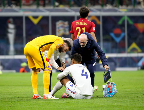 Injured, Raphael Varane of France - here with goalkeeper of France Hugo Lloris and physio of France Denis Morcel - will have to be replaced during...