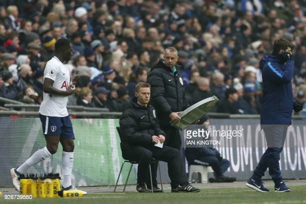Injured referee Michael Jones sits on the side lines as Tottenham Hotspur's Argentinian head coach Mauricio Pochettino looks on during the English...
