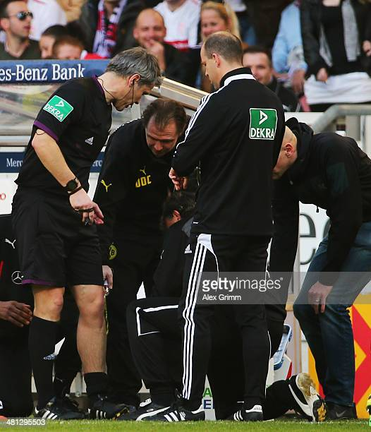 Injured referee Michael Weiner receives treatment during the Bundesliga match between VfB Stuttgart and Borussia Dortmund at MercedesBenz Arena on...