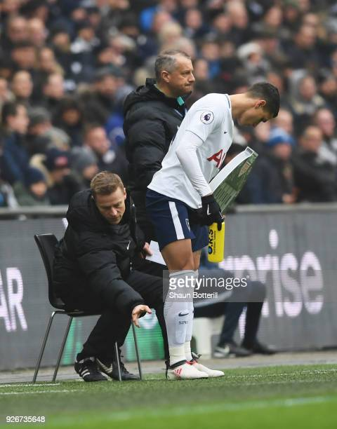 Injured referee Mike Jones checks Erik Lamela of Tottenham Hotspur as he operates as fourth official during the Premier League match between...